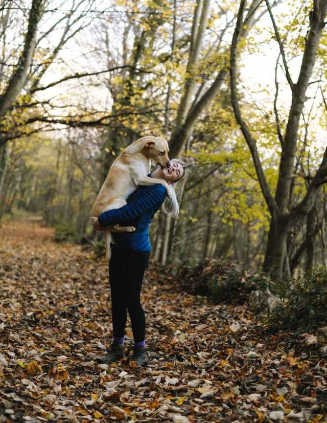 woman carrying dog while standing in the middle of the forest